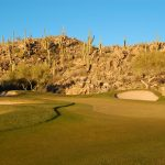 Green on the golf course at the Stone Canyon Club with rocky hills as scenery in Tucson Arizona